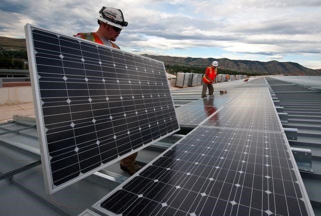 Workers installing solar panels on business roof